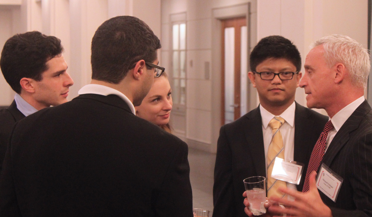 students talking to an alumnus