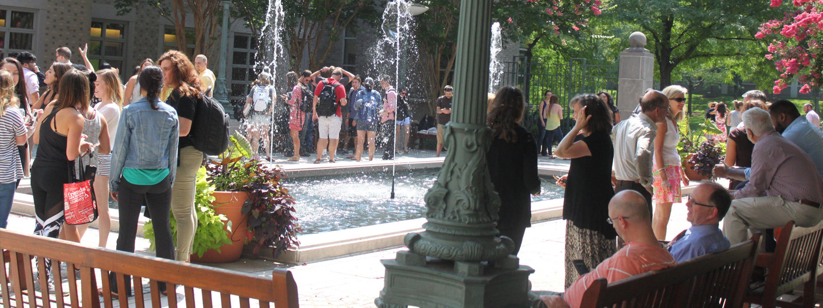 Group of law students and faculty outside of the law school by the fountain