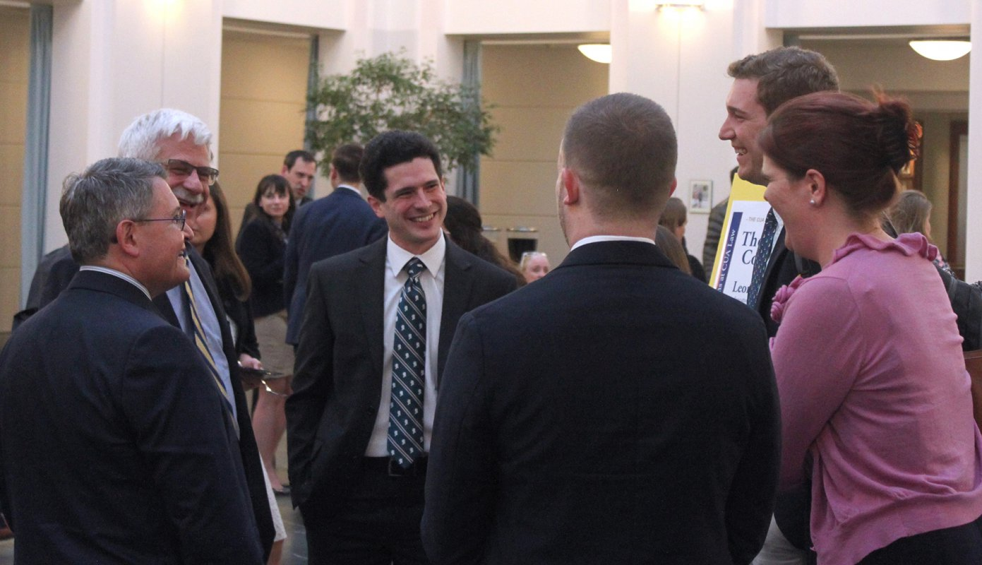 Leonard Leo talking with some students and alumni in the law school atrium